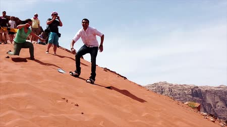 храбрость : Wadi Rum, Jordan - 2019-04-23 - Man Tries to Snowboard Down Sand Dune But Cannot Slide.