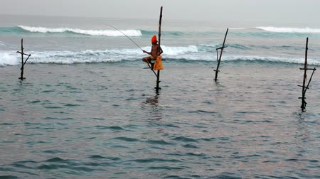 fishing pole : Galle, Sri Lanka - 2019-04-01 - Stilt Fishermen - One Man in Orange Turban.