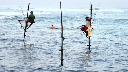 fisherman : Galle, Sri Lanka - 2019-04-01 - Stilt Fishermen - Two Men With Surfer Swimming Out.