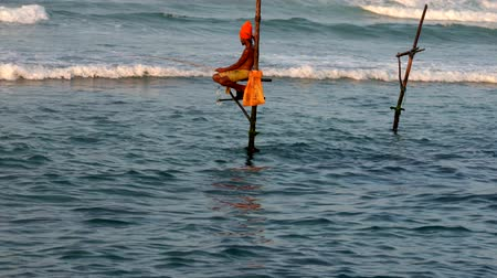 fisherman : Galle, Sri Lanka - 2019-04-01 - Stilt Fishermen - Orange Turban and Reflection.