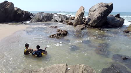 mates : Galle, Sri Lanka - 2019-04-01 - Two Boys and a Dog Play in Tidepool.