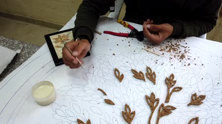 vleermuis : Petra, Jordan - 2019-04-20 - Mosaic 2 - Artists Glues Pieces for Flower Plaque. Stockvideo