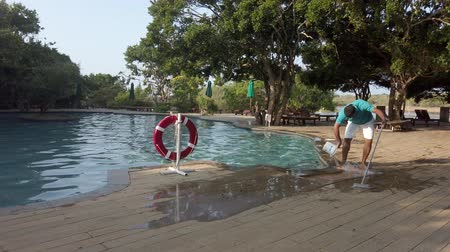 siatka : Galle, Sri Lanka - 2019-04-01 - Pool Maintenance Man Cleans Entry to Pool at Resort in Sri Lanka. Wideo