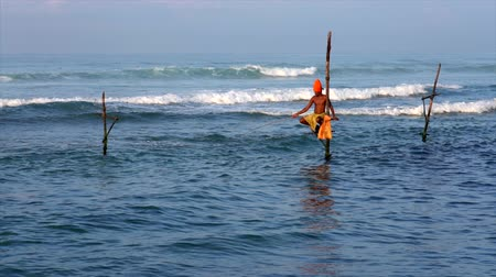 fishing pole : Galle, Sri Lanka - 2019-04-01 - Stilt Fishermen - Slow Motion Solo Man in Orange Turban.
