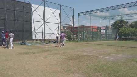 vleermuis : Galle, Sri Lanka - 2019-04-01 - Teenage Cricket Practice - Batting Cage Ball neemt Wild Bounce.