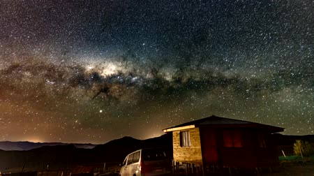 alpes : Vacuna, Chile - 2019-07-02 - Timelapse - Milky Way rotates over cabin as the sun rises. Stock Footage