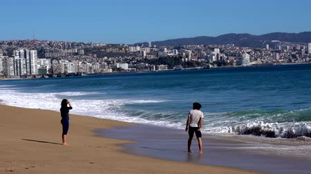 fürdés : Vina del Mar, Chile - 2019-07-28 - Young Couple Talk in the Surf.