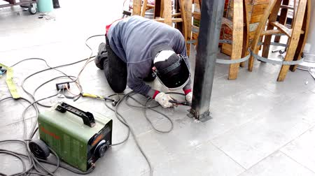 welding helmet : Valparaiso, Chile - 2019-07-19 - Man Welds Beam to Floor.