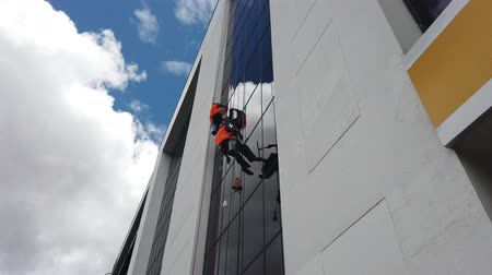 lano : Cuenca, Ecuador - 2019-02-09 - Window Washers Clean Glass Wall of Highrise Against Fluffy Clouds.