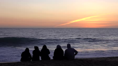 Vina del Mar, Chile - 2019-07-18 - Five Friends Sit on Beach Watching Sun Set In Front of Rough Surf.