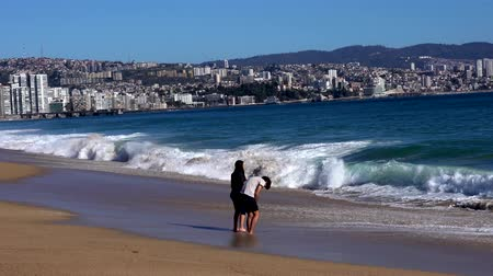fürdés : Vina del Mar, Chile - 2019-07-28 - Young Couple Stands in the Surf. Stock mozgókép