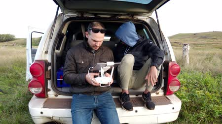 Father and Son Learn To Fly a Drone in Easter Island in Back of Car.