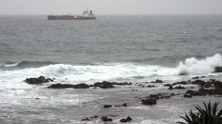 Waves Lap at Rocky Coast With Ship in Distance. Stock Footage