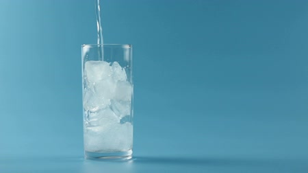 woda mineralna : Mineral water pouring in glass in blue background Wideo