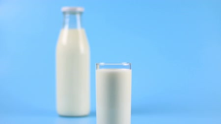 pivoting : A bottle of milk and a glass of milk on blue background