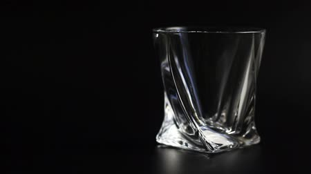 nightcap : Whiskey being poured into a glass against black background. Close up.