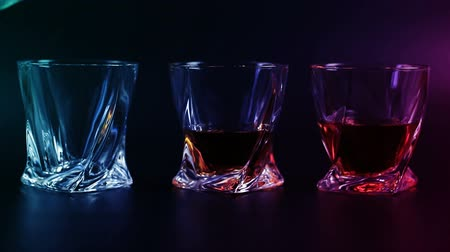 nightcap : Whiskey being poured into a glass against black background. Long shot.
