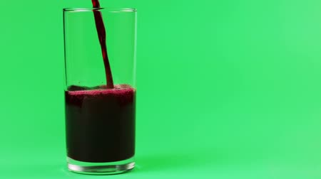 roma : cherry, grape,  Pomegranate juice is poured into a glass on a green background