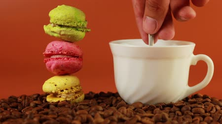macarons : Macrons with cup of coffee on a brown background Stock Footage