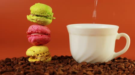 desszertek : Macrons with cup of coffee on a brown background Stock mozgókép