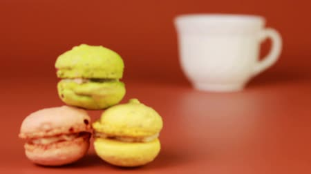 миндальное печенье : Cup of coffee with macaroons on a brown background.