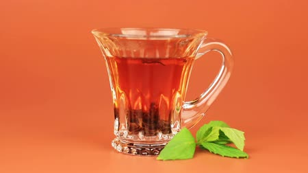 black tea : Glass cup tea with mint leaf on brown background.