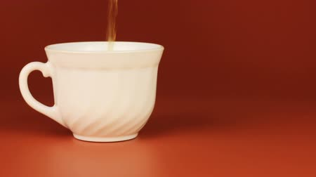 oregano : Tea being poured into tea cup on brown background.