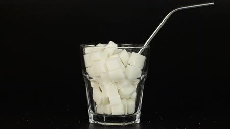 desszertek : Glass filled with white sugar cubes symbolizing the high content of sugar in our drinks and diet. Stock mozgókép