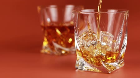 nightcap : Whiskey being poured into glass with ice cubes Stock Footage