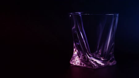 nightcap : Whiskey being poured into a glass against black background.