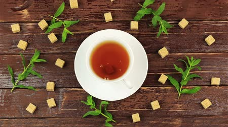 demlik : Sugar cubes added into tea glass on table with fresh mint leaves and brown sugar in cubes on brown wooden table