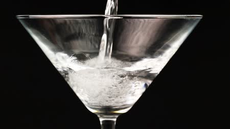 martini glasses : Pouring white cocktail in martini glass on black background Stock Footage