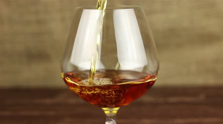 viski : Brandy being poured into a glass on wooden table Stok Video