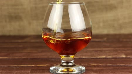 nightcap : Brandy being poured into a glass on wooden table Stock Footage
