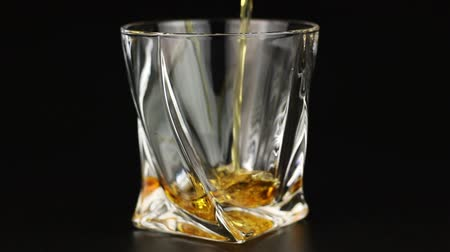 nightcap : Whiskey being poured into a glass on black background