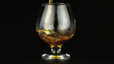nightcap : Brandy being poured into a glass on black background