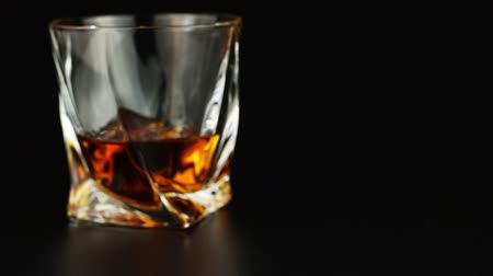 nightcap : Young man drinking whiskey over black background
