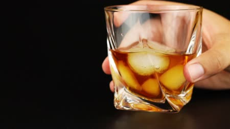 nightcap : Young man drinking whiskey with ice over black background Stock Footage