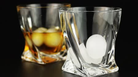 nightcap : Whiskey being poured into a glass with ice against a black background Stock Footage