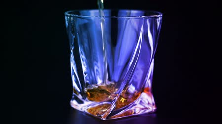 whisky : Whiskey being poured into a glass on black background