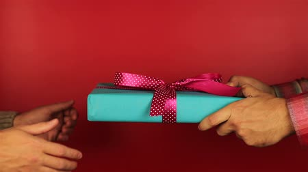 подарок : Young man gives a gift on red background. Blue gift box with purple ribbon opening. Congratulate Happy New Year, Merry Christmas, Happy Valentines Day, presents gifts