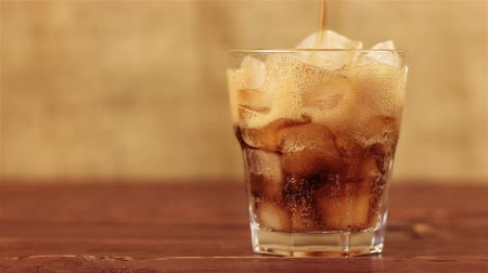pezseg : Cola with ice. Pouring Cola with Ice and bubbles in glass on a wooden table and brown background