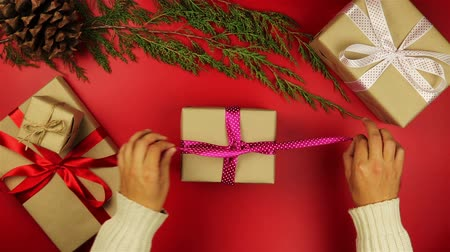 fából készült asztal : Top view hands unwrapping christmas presents on red background from above. Gift wrapped in brown paper and tied purple ribbon