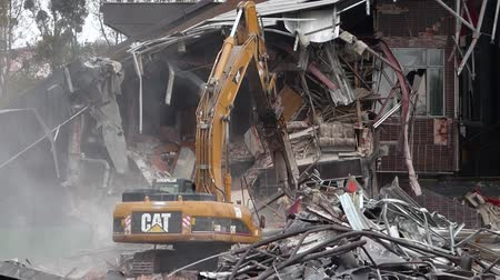 destroyed building : Demolition of old building by a yellow excavator Stock Footage