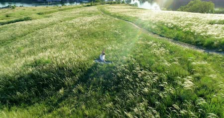 Girl meditates on a beautiful green meadow