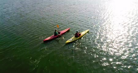 Two kayaks are sailing along a scenic river. Aerial view. Slow motion.