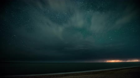 Time-lapse. Starry night with thunderstorm and lightning over the sea