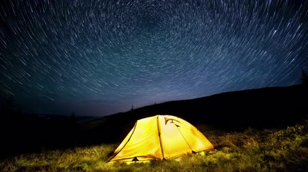 Time-lapse. Star circles above the glowing camping tent Stok Video