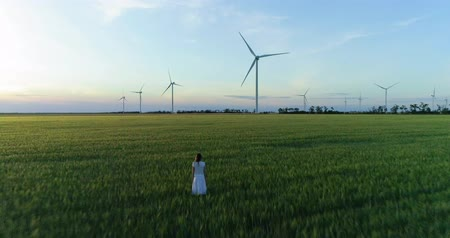 Beautiful girl standing on green field with windmills for electric power production Stok Video