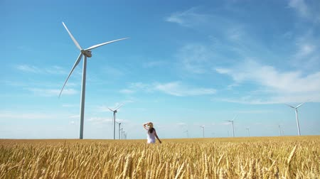 girl on yellow field of wheat with windmills